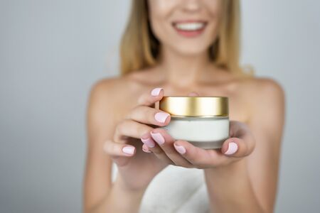 smiling attractive blond woman holding beauty cream in her hands close up isolated white background