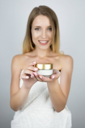 smiling attractive blond woman holding beauty cream in her hands isolated white background 写真素材