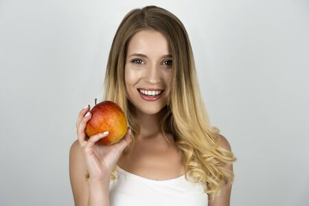 smiling blond attractive woman holding juicy apple in one hand isolated white background