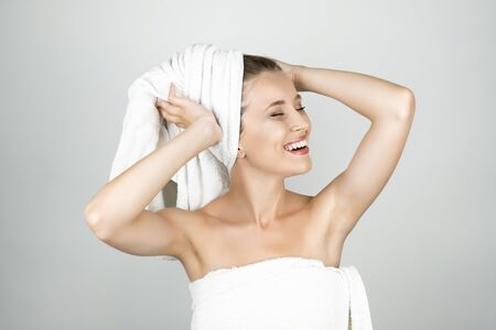 beautiful woman holding white towel on her head with arms up isolated white background Banque d'images
