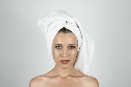 beautiful young woman in white towel on her head close up isolated white background