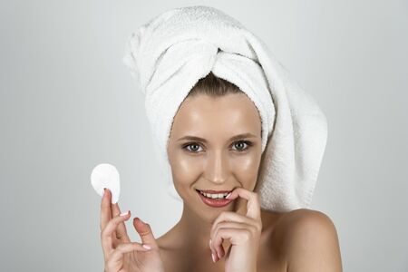 attractive blond woman in white towel on her head holding cotton pad in one hand and touching her tooth with her finger isolated white background