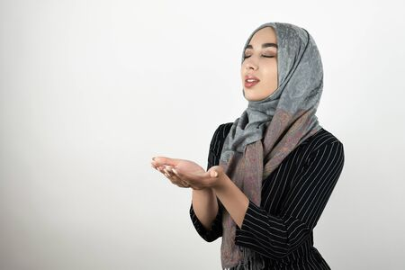 young beautiful hopeful Muslim woman wearing turban hijab, headscarf holding her hands together standing with closed eyes isolated white background