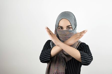 young attractive Muslim student wearing turban hijab headscarf saying no to war and violence holds her arms crossed isolated white background