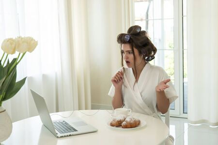 beautiful young surprised brunette in hair curlers and headphones having online conversation on her laptop while drinking coffee and eating croissants for breakfast in bright kitchen