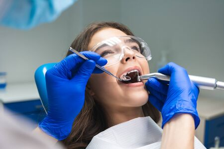 dentist in mask filling the patients root canal while she is lying on dental chair wearing safety glasses under the medical lamp in dental office
