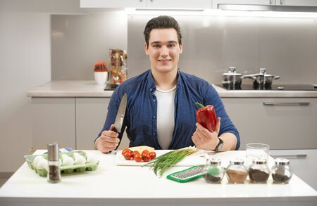 young handsome man sitting in bright kitchen preparing breakfast holding knife in one hand and fresh red pepper in another