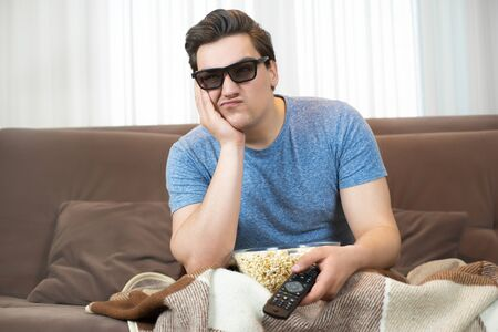 young handsome man wearing sunglasses watching movie eating popcorn clicking remote control looks disappointed