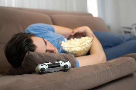 young handsome man fall asleep after playing fascinating video game still holding popcorn in his hands