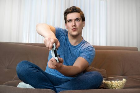 young handsome man playing video game sitting on comfy sofa holding joystick looking involved in mission Stock Photo