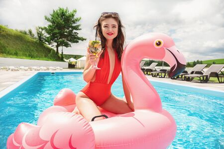 young brunette beautiful woman spending great time having fun at pool on pink flamingo drinking cocktail 免版税图像