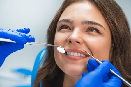 smiling happy brunette woman patient examined by dentist in blue gloves using dental mirror and scaler sitting in dental clinic