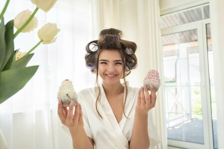 beautiful young smiling brunette woman in hair curlers holding two cupcakes in both hands standing in bright kitchen