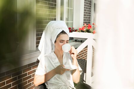 happy beautiful young brunette woman wearing dressing gown and white towel on her head enjoying cup of coffee on the terrace 免版税图像