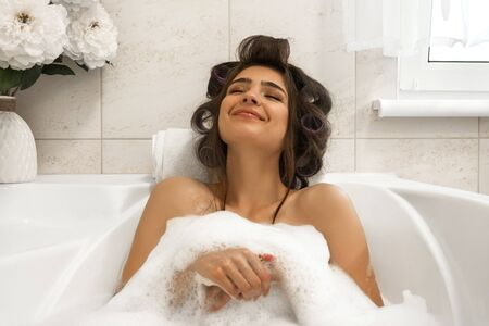 attractive young brunette woman in hair curlers enjoying her bath with foam in bright bathroom
