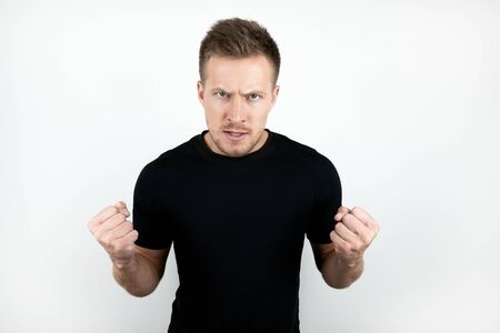 handsome young man wearing black t-shirt clenching his fists with anger isolated white background