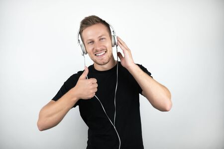handsome young man wearing black t-shirt listening to music in headphones showing ok sign on isolated white background