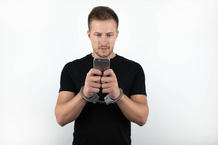 handsome young man in black t-shirt holding smartphone while being handcuffed on isolated white background Foto de archivo - 127996974