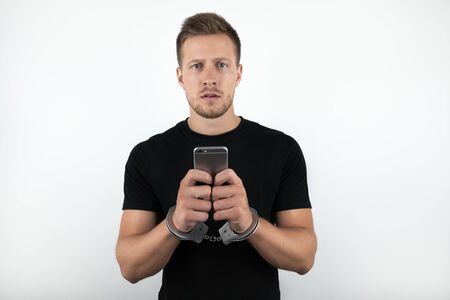 handsome young man wearing black t-shirt holding smartphone while being handcuffed on isolated white background Foto de archivo - 127996977