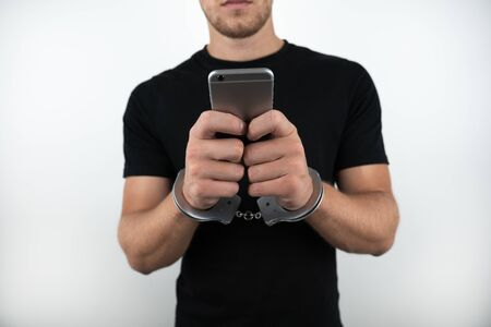man wearing black t-shirt holding smartphone while being handcuffed on isolated white background Foto de archivo