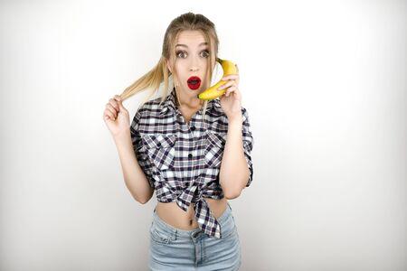 Joven hermosa mujer rubia vestida con camisa a cuadros de moda y pantalones cortos de mezclilla sosteniendo banana como un teléfono aislado fondo blanco. Foto de archivo