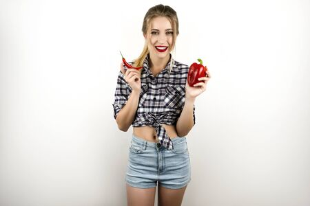 young beautiful blonde woman wearing trendy checkered shirt and denim shorts holding red chilly and red sweet pepper isolated white background