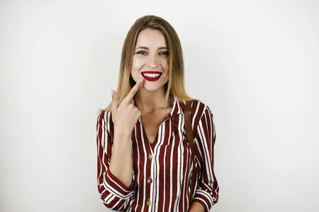 young beautiful blonde fit woman wearing trendy striped shirt showing healthy white teeth isolated white background Banque d'images - 129253188