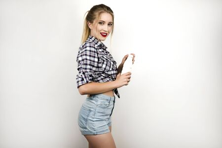 young beautiful blonde woman wearing trendy checkered shirt and denim shorts holding plastic bottle of yogurt isolated white background