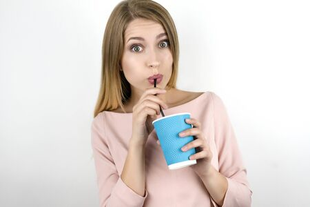 young beautiful blonde woman wearing trendy pink dress drinking coffee from blue paper cup takeaway isolated white background Zdjęcie Seryjne - 129253068