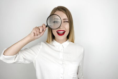 young beautiful blond woman holding magnifier near her eye isolated white background 版權商用圖片