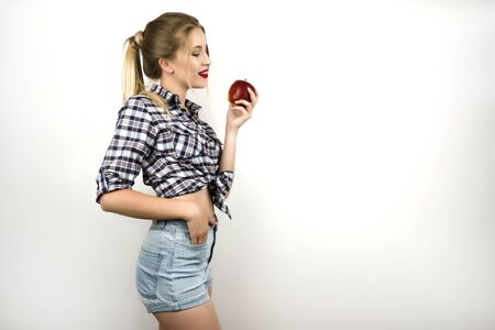 young beautiful blonde woman wearing trendy checkered shirt and denim shorts holding fresh apple isolated white background