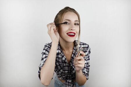 young beautiful gorgeous blonde woman wearing trendy checkered shirt and denim shorts applying lash mascara smiling isolated white background