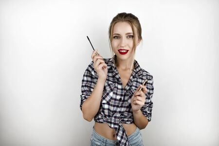 young beautiful gorgeous blonde woman wearing trendy checkered shirt and denim shorts holding lash mascara isolated white background
