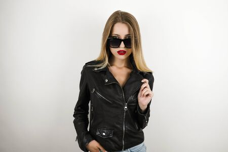young beautiful blonde sexy woman in sun glasses wearing leather jacket looks sexy isolated white background
