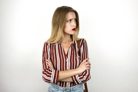 young beautiful blonde upset woman wearing trendy striped shirt denim shorts and leather mini bag isolated white background Banco de Imagens