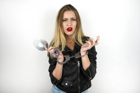 young beautiful blonde woman wearing black leather jacket looks confused being handcuffed with empty glass for alcohol on isolated white background Archivio Fotografico