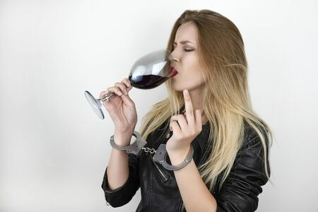 young beautiful blonde woman wearing black leather jacket drinks wine and shows off sign being handcuffed on isolated white background