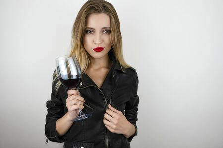 young beautiful sexy blonde woman wearing black leather jacket holds glass of wine on isolated white background