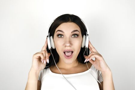 brunette young woman listening her favourite songs in headphones looking funny on isolated white background
