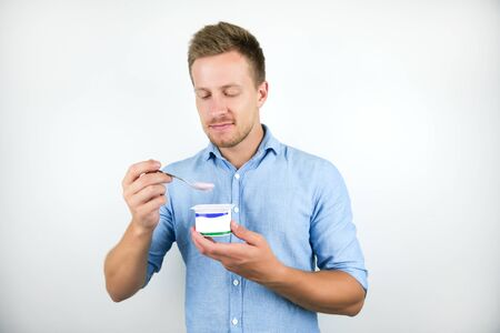 young handsome man eats yogurt with spoon on isolated white background