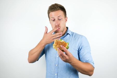 young handsome man enjoying cheeseburger from fast food restaurant licking his fingers while eating on isolated white background