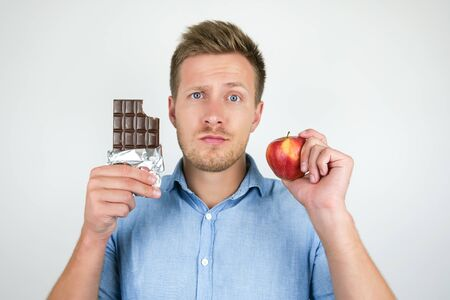 young handsome man holding chocolate bar in one hand and fresh ripe apple in another showing contrast on isolated white background
