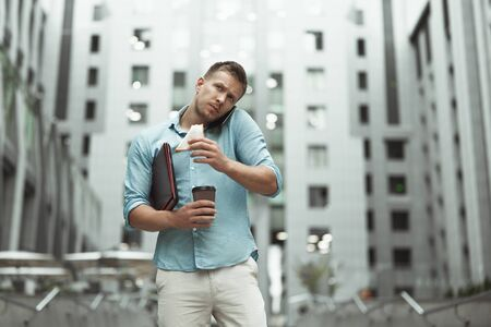 young handsome office worker talking on phone holding laptop and cup of coffee eating sandwich walking down the street near business center Foto de archivo