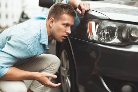 young handsome man sitting near his car after crush looking surprised Zdjęcie Seryjne