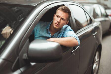 Jeune bel homme au volant de sa voiture à nerveux coincé dans les embouteillages