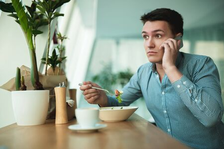 young handsome man speaks on the phone while eating salad and drinking coffee for lunch during break at cafe near office looks astonished