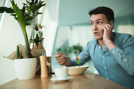 young handsome man speaks on the phone while eating salad and drinking coffee for lunch during break at cafe near office looks worried
