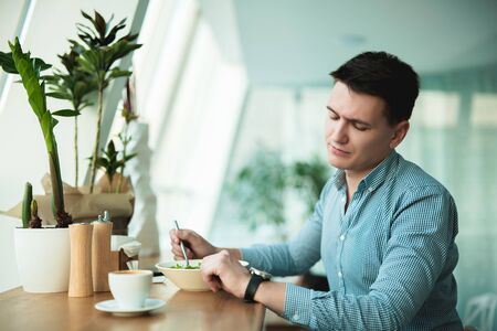 young handsome man looks at his wristwatch while eating salad and drinking coffee during break at cafe waiting for his patner to come Archivio Fotografico