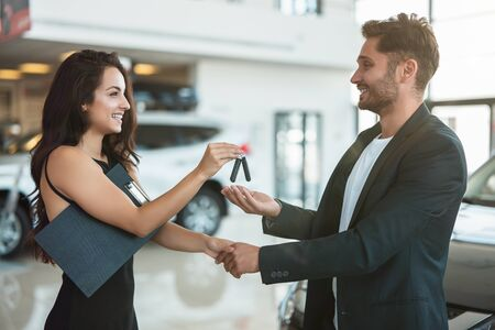 Hermosa joven gerente dando las llaves del auto al apuesto cliente de pie cerca de un auto nuevo después de un trato exitoso en el centro de la concesionaria sintiéndose feliz Foto de archivo