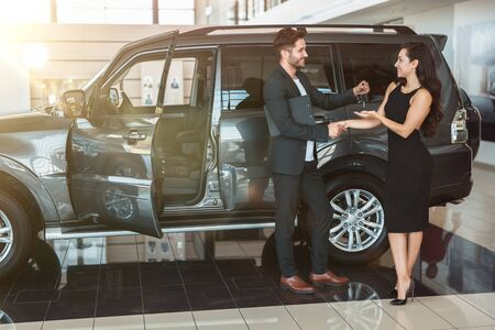 handsome man manager gives car keys to beautiful brunette woman client after succesful deal in dealership center standing near new SUV Foto de archivo